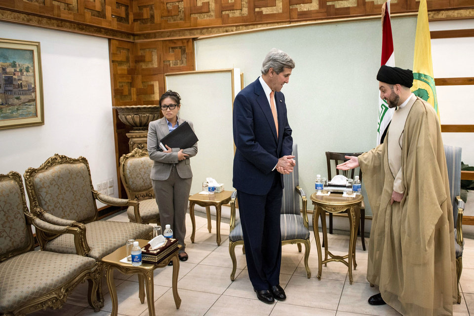 Photo - Ammar al-Hakim, right, head of the Shiite Supreme Islamic Iraqi Council, welcomes U.S. Secretary of State John Kerry, center, in Baghdad on Monday, June 23, 2014.  Kerry flew to Baghdad on Monday to meet with Iraq's leaders and personally urge the Shiite-led government to give more power to political opponents before a Sunni insurgency seizes more control across the country and sweeps away hopes for lasting peace.(AP Photo/Brendan Smialowski, Pool)