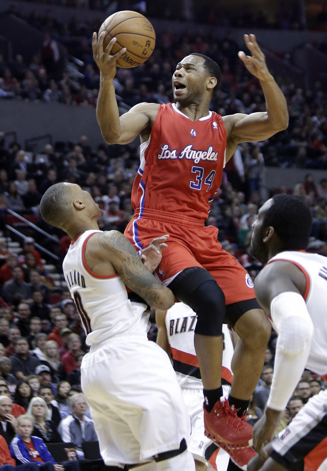Los Angeles Clippers guard Willie Green, middle, goes up for a shot between the Portland Trail Blazers Damian Lillard, left, and J.J. Hickson during the first quarter of an NBA basketball game in Portland, Ore., Saturday, Jan. 26, 2013.(AP Photo/Don Ryan)