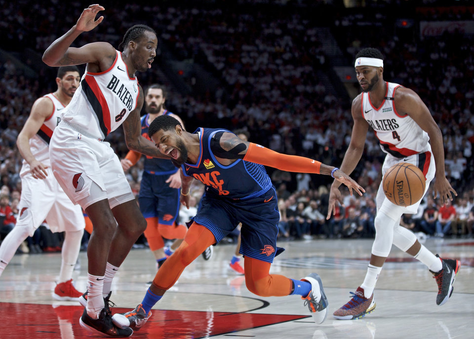 Photo - Oklahoma City Thunder forward Paul George, center, loses the ball in front of Portland Trail Blazers forward Al-Farouq Aminu, left, and forward Maurice Harkless, right, during the first half of Game 5 of an NBA basketball first-round playoff series, Tuesday, April 23, 2019, in Portland, Ore. (AP Photo/Craig Mitchelldyer)
