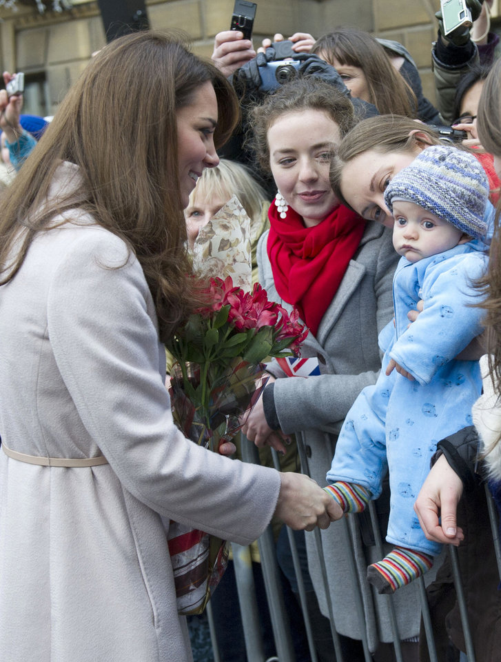 FILE - In this Wednesday Nov. 28, 2012 file photo Britain's Kate Duchess of Cambridge. left. meets with a young member of the public as she arrives at the Guildhall during a visit to Cambridge England. Prince William's wife Kate has been admitted to the hospital in early stages of labor it was announced on Monday July 22, 2013.  (AP Photo/Arthur Edwards, File)