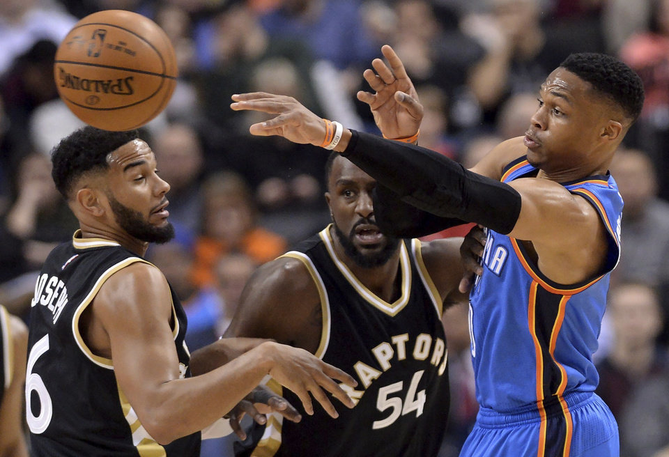 Photo - Oklahoma City Thunder guard Russell Westbrook (0) moves the ball past Toronto Raptors guard Cory Joseph (6) and forward Patrick Patterson (54) during the first half of an NBA basketball game Thursday, March 16, 2017, in Toronto. (Nathan Denette/The Canadian Press via AP)