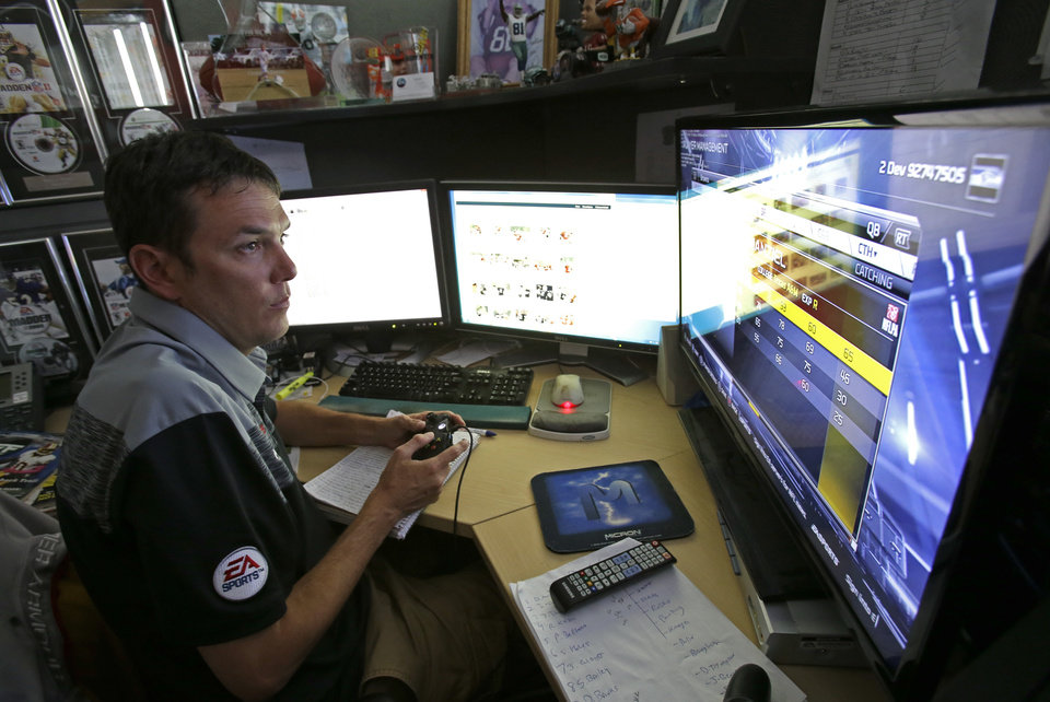 Photo - In this Wednesday, Aug. 6, 2014 photo, Donny Moore works at three computer screens as he rates NFL football players for the Madden NFL video football game at EA Sports in Orlando, Fla.  Moore is the