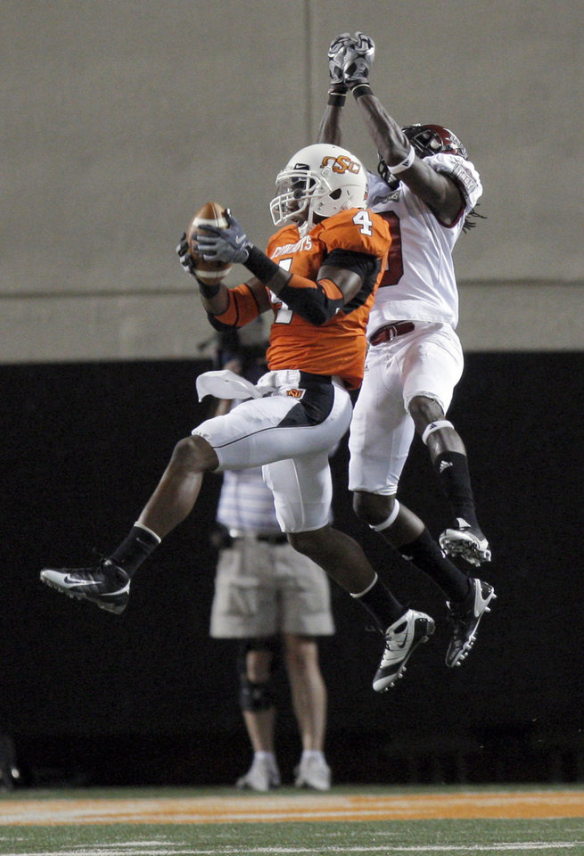 Photo - OSU's Justin Gilbert (4) makes an apparent interception on a pass intended for Troy's Jason Bruce (9). The interception was called back after a penalty on the play during the college football game between the Oklahoma State University Cowboys (OSU) and the Troy University Trojans at Boone Pickens Stadium in Stillwater, Okla., Saturday, Sept. 11, 2010. Photo by Sarah Phipps, The Oklahoman