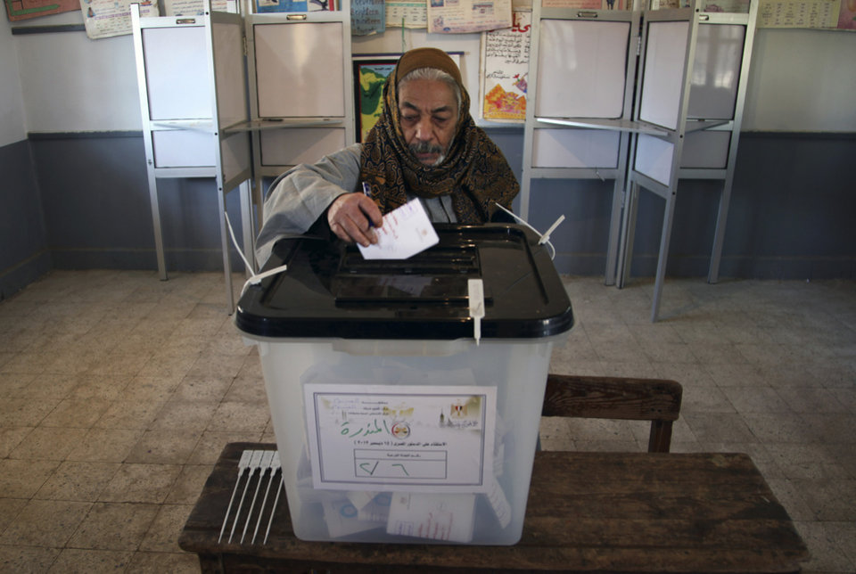 Photo - An Egyptian man casts his vote during the second round of a referendum on a disputed constitution drafted by Islamist supporters of President Mohammed Morsi in Fayoum, about 100 kilometers (62 miles) south of Cairo, Egypt, Saturday, Dec. 22, 2012.(AP Photo/Khalil Hamra)