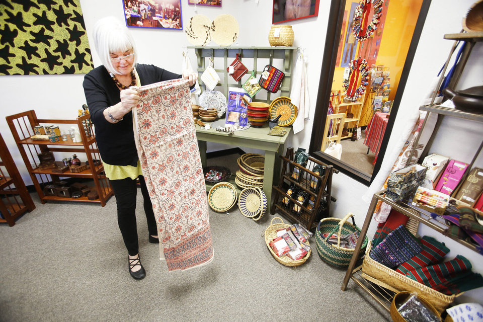 Photo - Volunteer Suzie Hupfeld folds a tablecloth at the PAMBE Ghana Global Market in Oklahoma City.  Steve Gooch - The Oklahoman