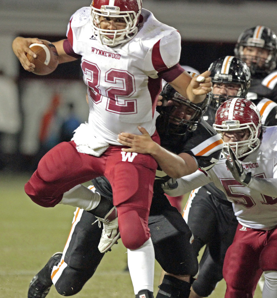 Photo - Wynnewood's Trey Knowles (32) drags a tackler as the Wayne Bulldogs play the Wynnewood Savages in District 5, Class A high school football on Friday, Oct. 28, 2011, in Wayne, Okla.    Photo by Steve Sisney, The Oklahoman