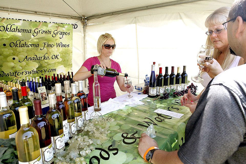 Charity Middleton pours wine for Rhonda and Eric Brinsfield, of Midwest City, at the 2012 Made in Oklahoma Festival.  Photo by Jim Beckel, The Oklahoman Archives