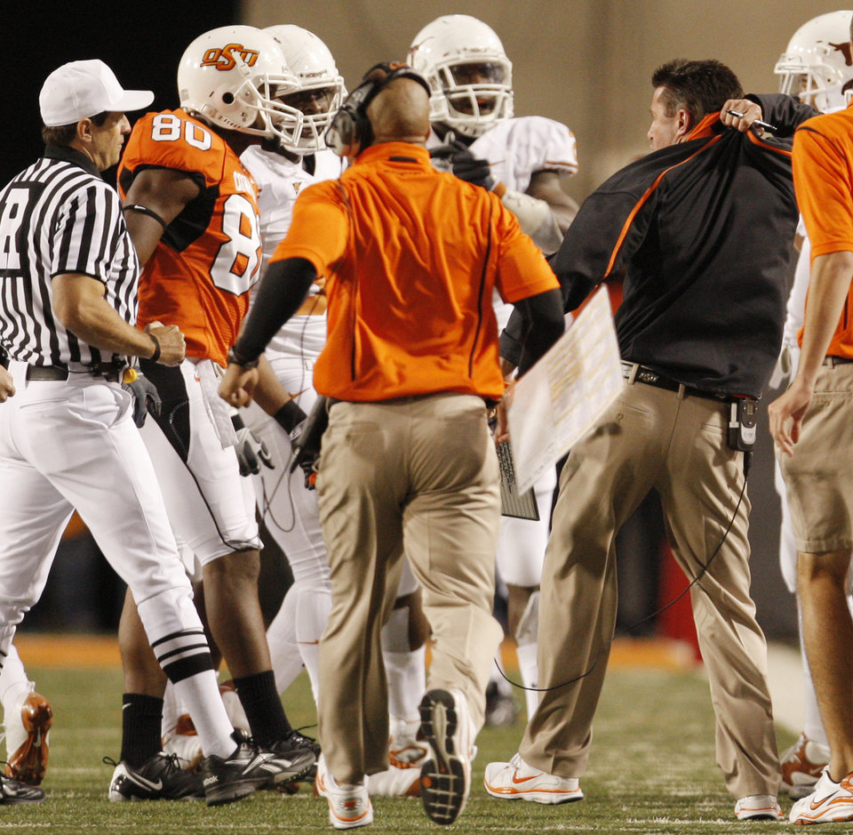 Photo - Head coach Mike Gundy complains to the officials that Zac Robinson was hog collared during the college football game between the Oklahoma State University Cowboys (OSU) and the University of Texas Longhorns (UT) at Boone Pickens Stadium in Stillwater, Okla., Saturday, Oct. 31, 2009. Photo by Doug Hoke, The Oklahoman