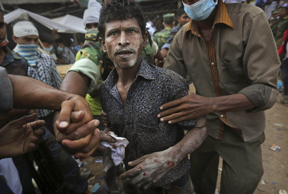 Photo - A Bangladeshi garment worker who soldiers said  was pulled alive from the rubble reacts as he walk on his own at the site of a building that collapsed Wednesday in Savar, near Dhaka, Bangladesh, Friday, April 26, 2013. By Friday, the death toll reached hundreds of people as rescuers continued to search for injured and missing, after a huge section of an eight-story building that housed several garment factories splintered into a pile of concrete.(AP Photo/Kevin Frayer)