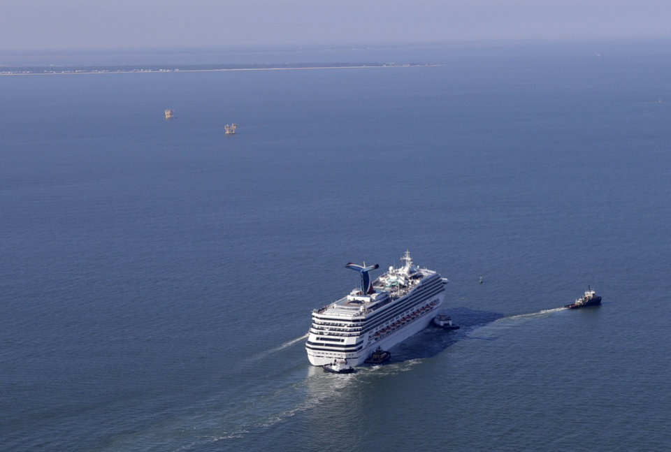 Photo - A disabled Carnival Lines cruise ship is towed to harbor off Mobile Bay, Ala., Thursday, Feb. 14, 2013.  The ship with more than 4,200 passengers and crew members has been idled for nearly a week in the Gulf of Mexico following an engine room fire. (AP Photo/Gerald Herbert)