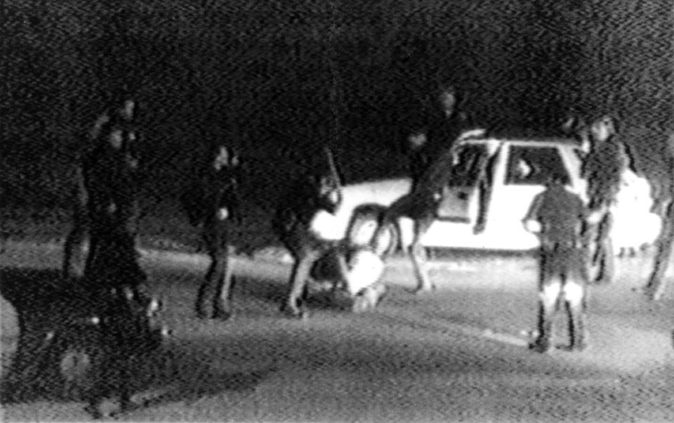 Photo -   FILE - This March 31, 1991 frame from a video tape shot by George Holliday from his apartment in a suburb of Los Angeles shows what appears to be a group of police officers beating a man with nightsticks and kicking him as other officers look on. The April 29, 1992 acquittal of four police officers in the beating sparked rioting that spread across the city and into neighboring suburbs. Cars were demolished and homes and businesses were burned. Before order was restored, 55 people were dead, 2,300 injured and more than 1,500 buildings were damaged or destroyed.(AP Photo/George Holliday/Courtesy of KTLA Los Angeles)