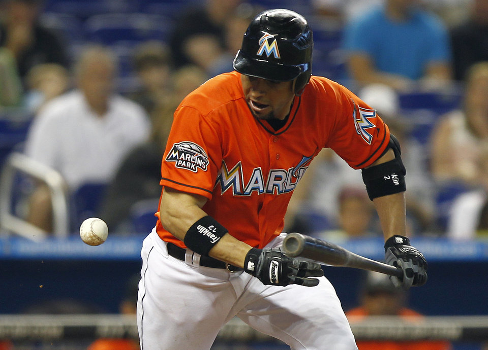 Photo -   Miami Marlins batter Omar Infante watches his bouncing, bunted ball as he runs to first during the second inning of a baseball game against the Toronto Blue Jays in Miami, Saturday, June 23, 2012 . Infante was out at first. (AP Photo/J Pat Carter)