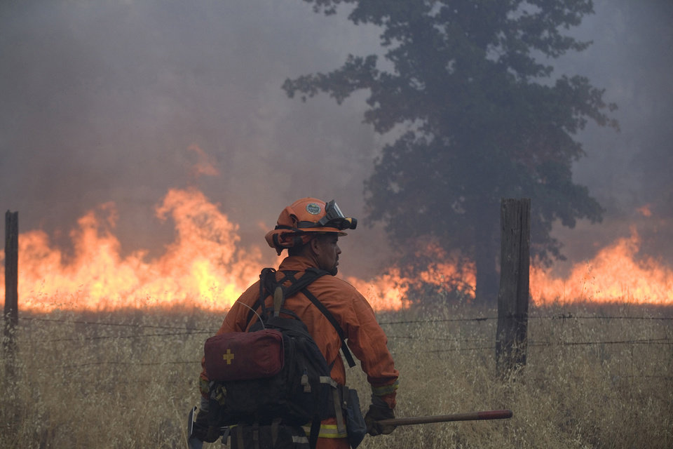Photo - FILE - In this July 11, 2014 photo, a member of an inmate firefighting crew works on the Bully fire  near Ono, Calif.  A 27-year-old man who was allegedly at an illegal marijuana plot is suspected of starting a wildfire that has burned about 6 square miles of forested land in northern California. Freddie Alexander Smoke III was arrested Saturday, July 12, 2014 and accused of recklessly causing a fire and with marijuana cultivation, both felonies, according to the California Department of Fire and Forestry Protection.   The so-called Bully fire has since grown to 3,700 acres and destroyed six structures, CalFire officials said.  The blaze, which is burning in steep terrain, was just 10 percent contained Sunday morning. (AP Photo/The Record Searchlight, Greg Barnette)