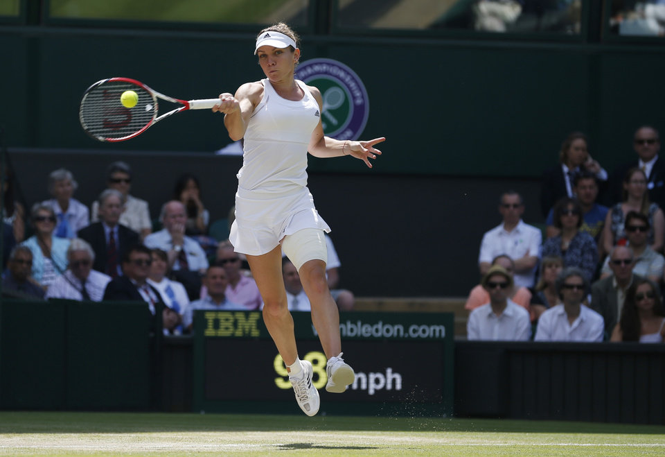 Photo - Simona Halep of Romania plays a return to Sabine Lisicki of Germany during their women's singles quarterfinal match at the All England Lawn Tennis Championships in Wimbledon, London, Wednesday, July 2, 2014. (AP Photo/Pavel Golovkin)
