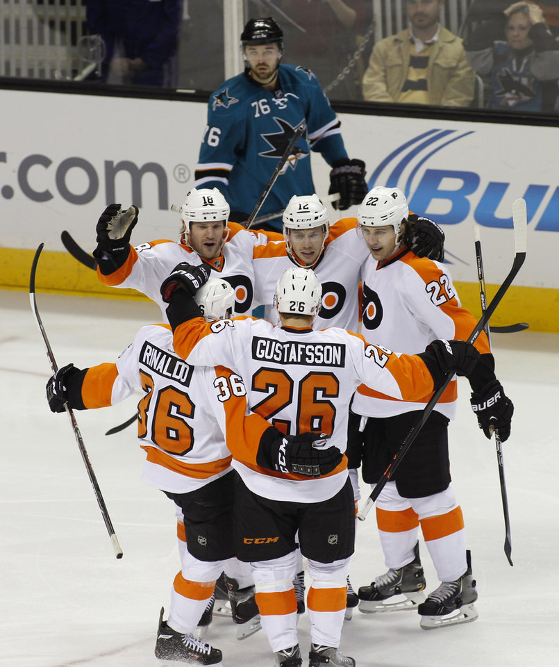 Photo - Philadelphia Flyers' Michael Raffi, center of group facing camera, celebrates with teammates, Adam Hall, left facing camera, Luke Schenn (22), Zac Rinaldo (36) and Erik Gustafsson (26) after scoring a goal against the San Jose Sharks during the third period of an NHL hockey game, Monday, Feb. 3, 2014, in San Jose, Calif. Sharks' Eriah Hayes is in the background. (AP Photo/George Nikitin)