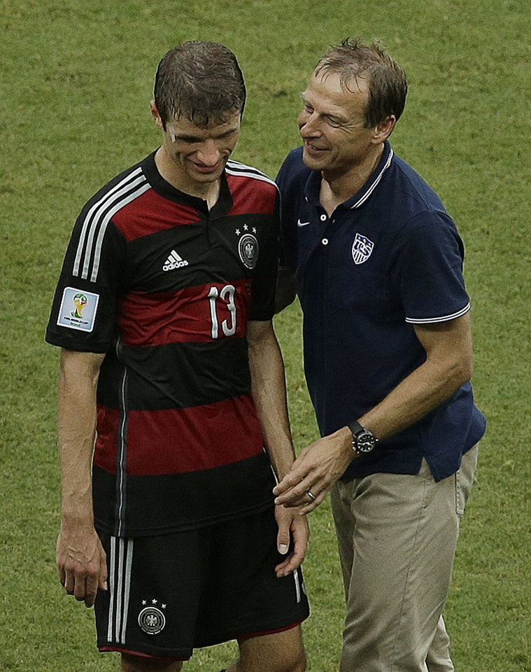 Photo - United States' head coach Juergen Klinsmann, right, greets Germany's Thomas Mueller after Germany beat the United States 1-0 during the group G World Cup soccer match between the USA and Germany at the Arena Pernambuco in Recife, Brazil, Thursday, June 26, 2014. (AP Photo/Hassan Ammar)