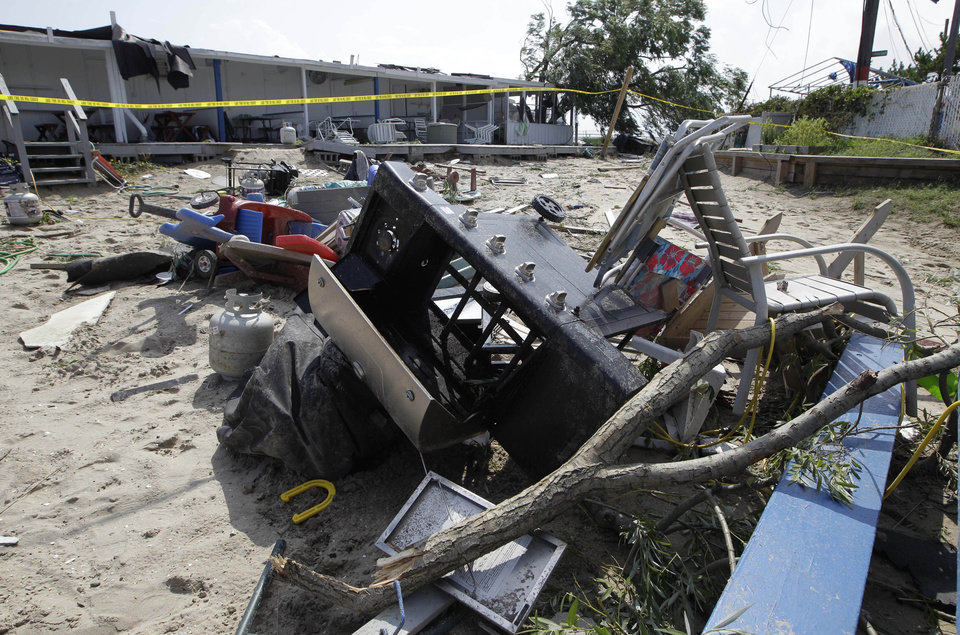 Photo -   A pile of debris, including a gas barbecue and propane tank, lie in the sand in front of cabanas at the Breezy Point Surf Club which was damaged by a possible tornado during severe weather in New York, Saturday, Sept. 8, 2012. A tornado swept out of the sea and hit the beachfront neighborhood in New York City, hurling debris in the air, knocking out power and startling residents who once thought of twisters as a Midwestern phenomenon. Firefighters were still assessing the damage, but no serious injuries were reported and the area affected by the storm appeared small. (AP Photo/Kathy Willens)