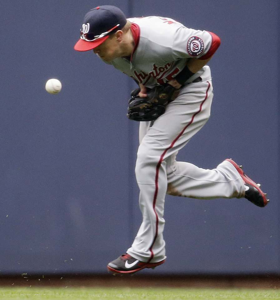 Photo - Washington Nationals' Nate McLouth has trouble with a two-run scoring hit by Milwaukee Brewers' Khris Davis during the fifth inning of a baseball game Wednesday, June 25, 2014, in Milwaukee. (AP Photo/Morry Gash)