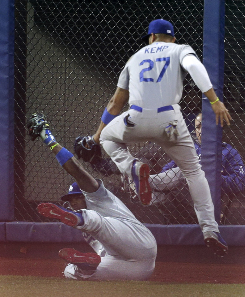 Photo - Los Angeles Dodgers center fielder Matt Kemp (27) leaps over right fielder Yasiel Puig (66) as Puig holds up a diving catch on a ball hit by New York Mets' Wilmer Flores during the second inning of a baseball game, Thursday, May 22, 2014, in New York. (AP Photo/Julie Jacobson)