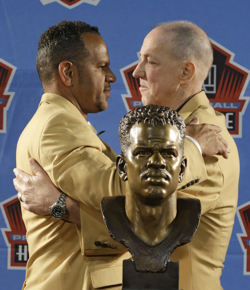Photo - Hall of Fame inductee Andre Reed, left, and former Buffalo Bills quarterback Jim Kelly hug during the Pro Football Hall of Fame enshrinement ceremony Saturday, Aug. 2, 2014, in Canton, Ohio. (AP Photo/Tony Dejak)