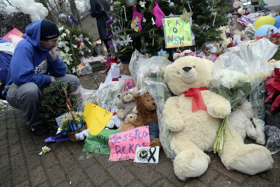 Photo - A]mourner pays his respects at one of the makeshift memorials for the Sandy Hook elementary shooting, Monday,Dec. 17, 2012 in Newtown, Conn. Authorities say a gunman killed his mother at their home and then opened fire inside the Sandy Hook Elementary School in Newtown, killing 26 people, including 20 children, before taking his own life, on Friday. (AP Photo/Mary Altaffer) ORG XMIT: CTMA109