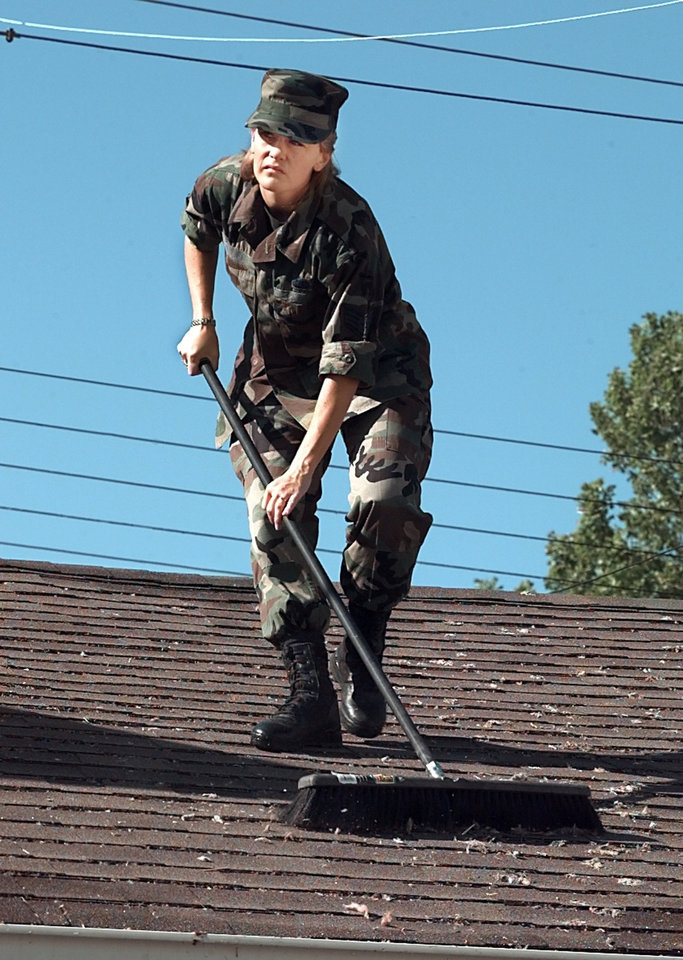 Tornado damage - cleanup: Sgt. Kristen Voice of the 72nd Services Squadron sweeping debris off the roof of a housing unit at Tinker Air Force Base.