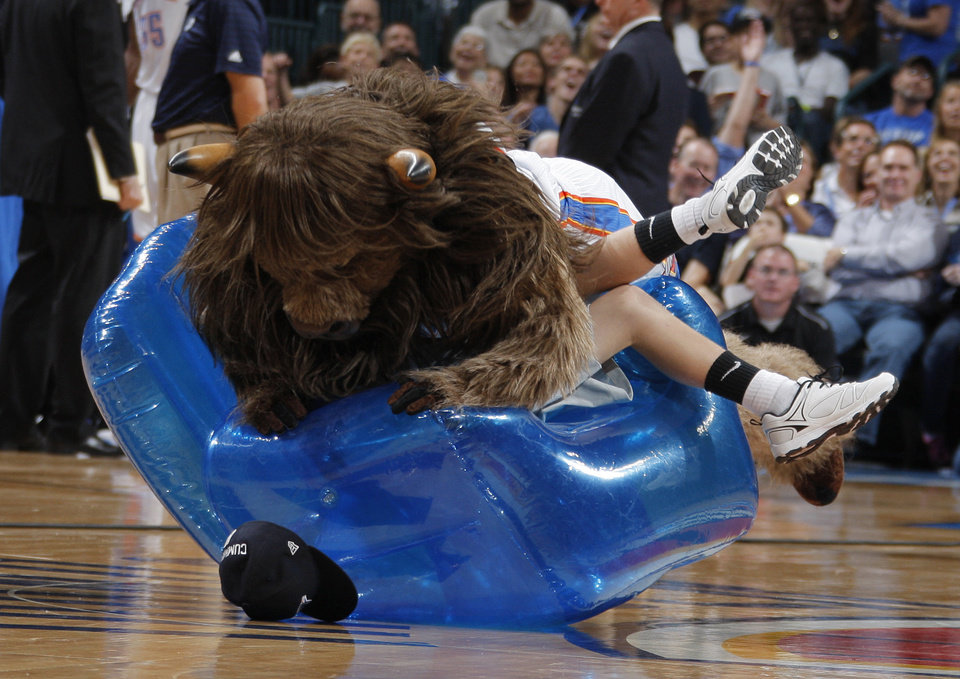 Photo - Rumble tackles a child while playing musical chairs during timeout during the NBA preseason basketball game between the Oklahoma City Thunder and the Denver Nuggets at the Chesapeake Energy Arena, Sunday, Oct. 21, 2012. Photo by Garett Fisbeck, The Oklahoman