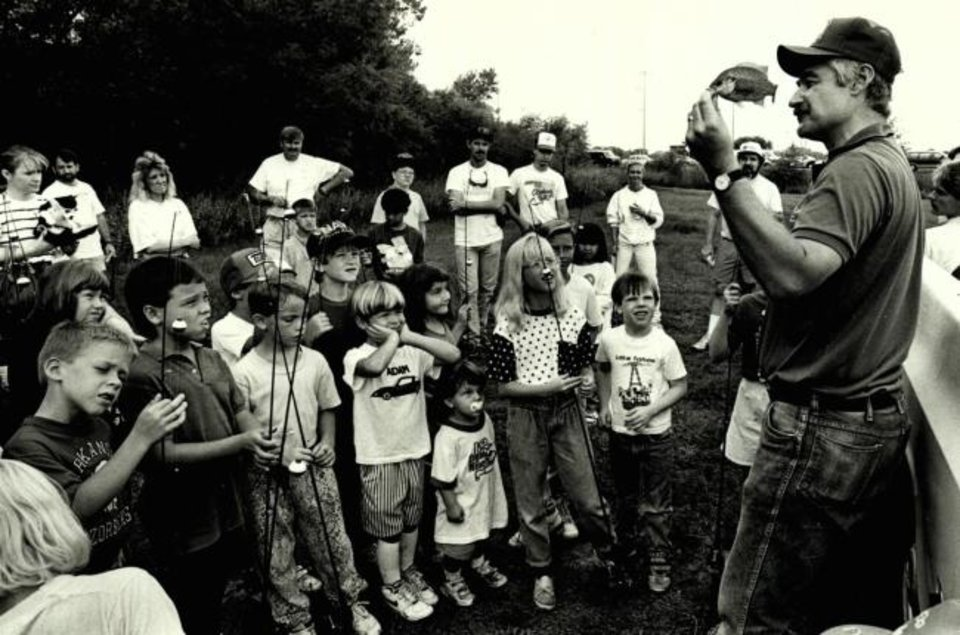 Photo -  Oklahoma City fisheries biologist Bob Martin holds up a sunfish to show to kids during a fishing clinic in 1991. [THE OKLAHOMAN ARCHIVES]