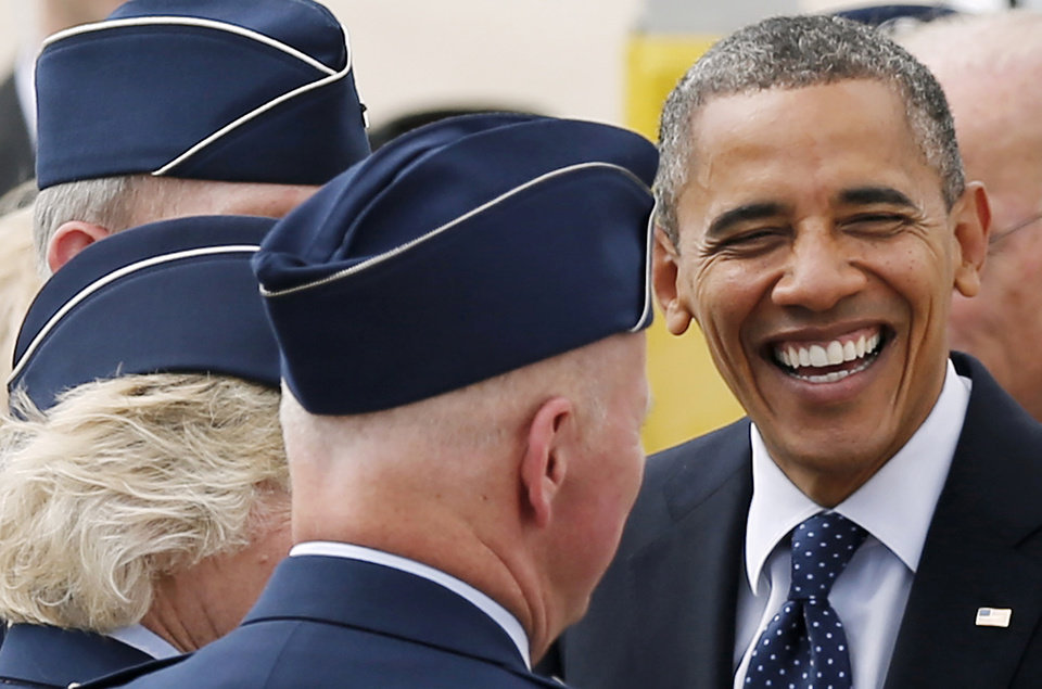 Photo -   President Barack Obama shares a laugh with service members upon his arrival at Pease Air National Guard Base in Portsmouth, N.H., Friday, Sept. 7, 2012. (AP Photo/Winslow Townson)