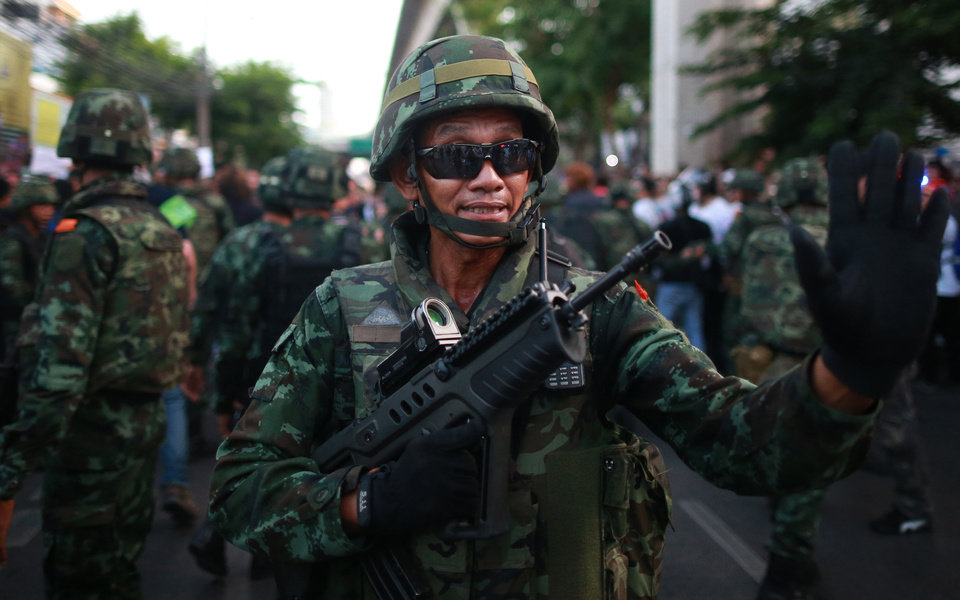 Photo - A Thai soldier gestures after being reinforced at the Victory Monument during an anti-coup demonstration in Bangkok, Thailand, Saturday, May 24, 2014. Thailand's coup leaders said Saturday that they would keep former Prime Minister Yingluck Shinawatra, Cabinet members and anti-government protest leaders detained for up to a week to give them
