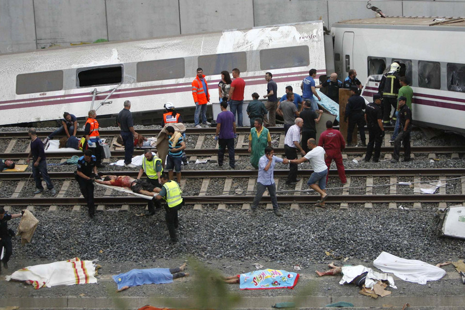 Photo - Emergency personnel respond to the scene of a train derailment in Santiago de Compostela, Spain, Wednesday, July 24, 2013. A train derailed in northwestern Spain on Wednesday night, toppling passenger cars on their sides and leaving at least one torn open as smoke rose into the air. Dozens were feared dead, with possibly even more injured. (AP Photo/ El correo Gallego/Antonio Hernandez)