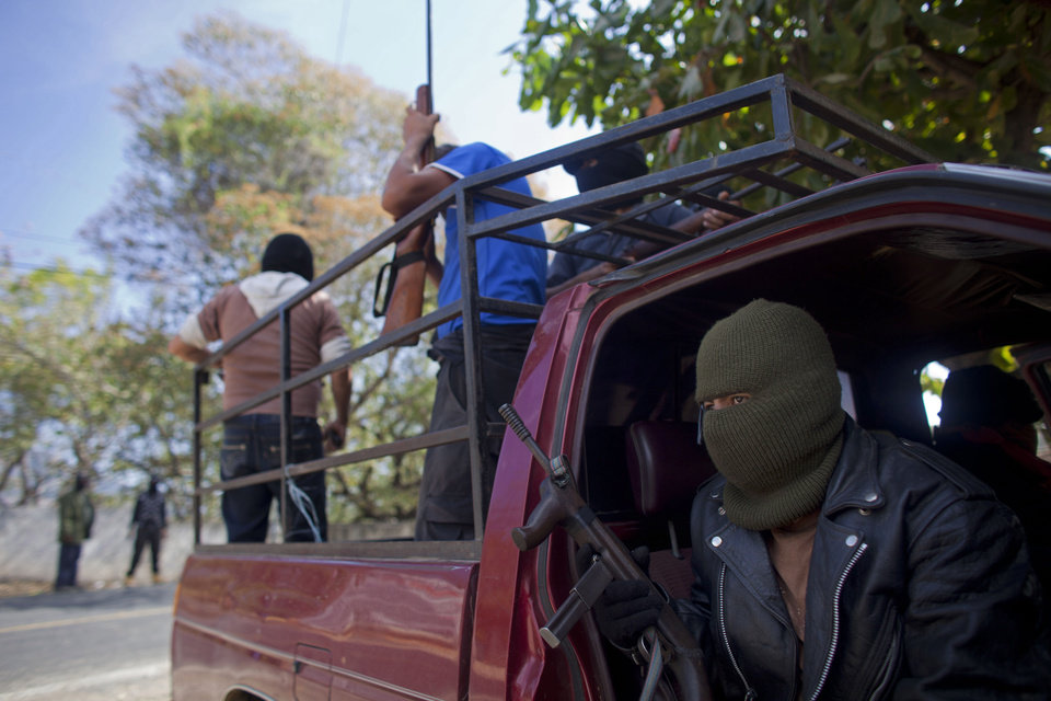 In this photo taken Friday Jan. 18, 2013, masked and armed men guard a roadblock in Las Mesas, near the town of Ayutla, Mexico.Hundreds of  men in the southern Mexico state of Guerrero have taken up arms to defend their villages against drug gangs, a vigilante movement born of frustration at extortion, killings and kidnappings in a region wracked by violence. (AP Photo/Dario Lopez-Mills)