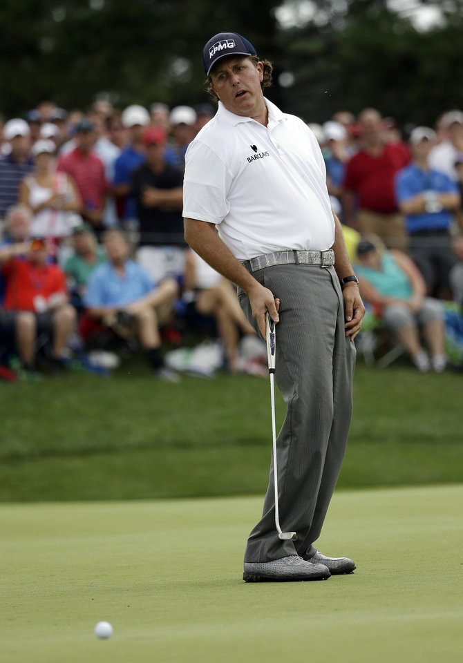 Photo - Phil Mickelson reacts to missing his eagle putt on the seventh hole during the third round of the PGA Championship golf tournament at Valhalla Golf Club on Saturday, Aug. 9, 2014, in Louisville, Ky. (AP Photo/David J. Phillip)