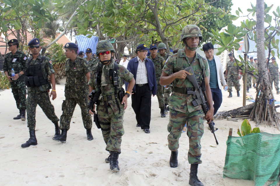 Photo - Armed Thai soldiers and local officials inspect the Patong beach during a clean up operation Wednesday, July 9, 2014, in Phuket, southern Thailand. Thailand's new military junta sent soldiers to one of the country's best known beaches Wednesday to evict food hawkers, massage huts and other illegal vendors as part of a campaign to clean-up the country's image and enforce laws that have long been ignored. (AP Photo/Krissada Mueanhawong)