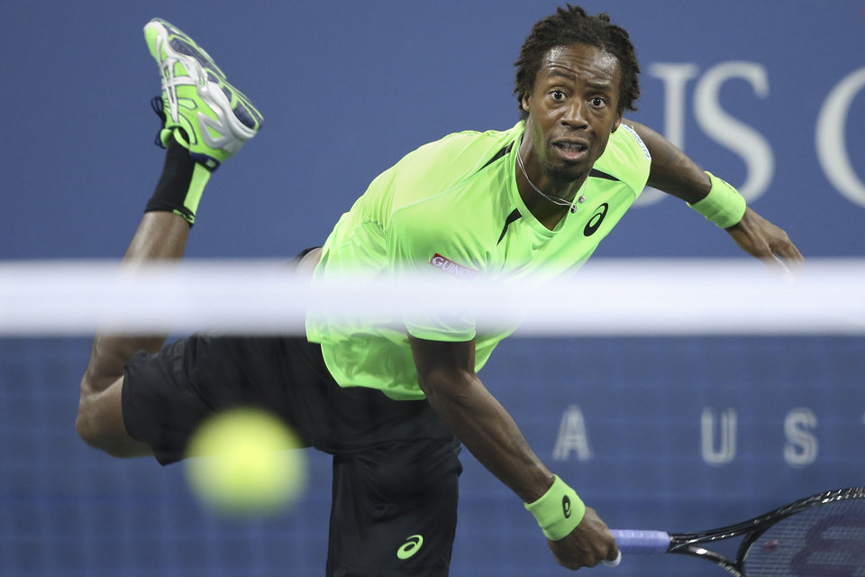 Photo - Gael Monfils, of France, watches a serve to Roger Federer, of Switzerland, during the quarterfinals of the U.S. Open tennis tournament, Thursday, Sept. 4, 2014, in New York. (AP Photo/John Minchillo)