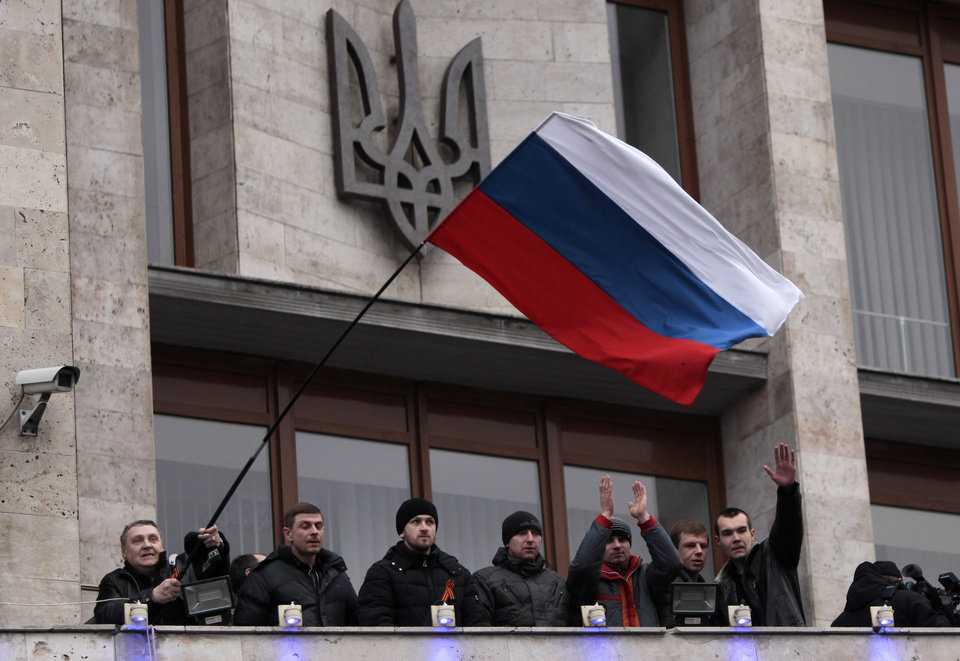 Photo - Pro-Russia demonstrators holding a Russian flag, with the Ukrainian emblem in the background, stand on the balcony of the regional administrative building after storming it in Donetsk, Ukraine, Wednesday, March 5, 2014. Hundreds of demonstrators waving Russian flags have stormed a government building in Donetsk in the eastern Ukraine. The region is the home area of fugitive Ukrainian President Viktor Yanukovych, who fled the country after massive protests in Kiev. (AP Photo/Sergei Chuzavkov)