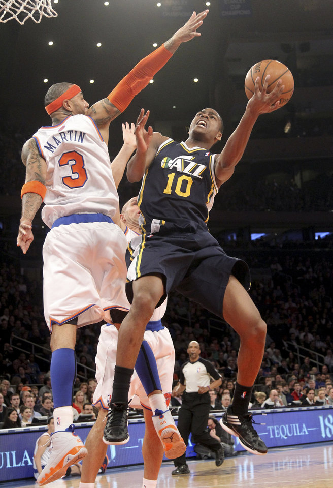 Photo - Utah Jazz's Alec Burks (10) goes up against New York Knicks Kenyon Martin during the first half of an NBA basketball game on Saturday, March 9, 2013, at Madison Square Garden in New York. (AP Photo/Mary Altaffer)