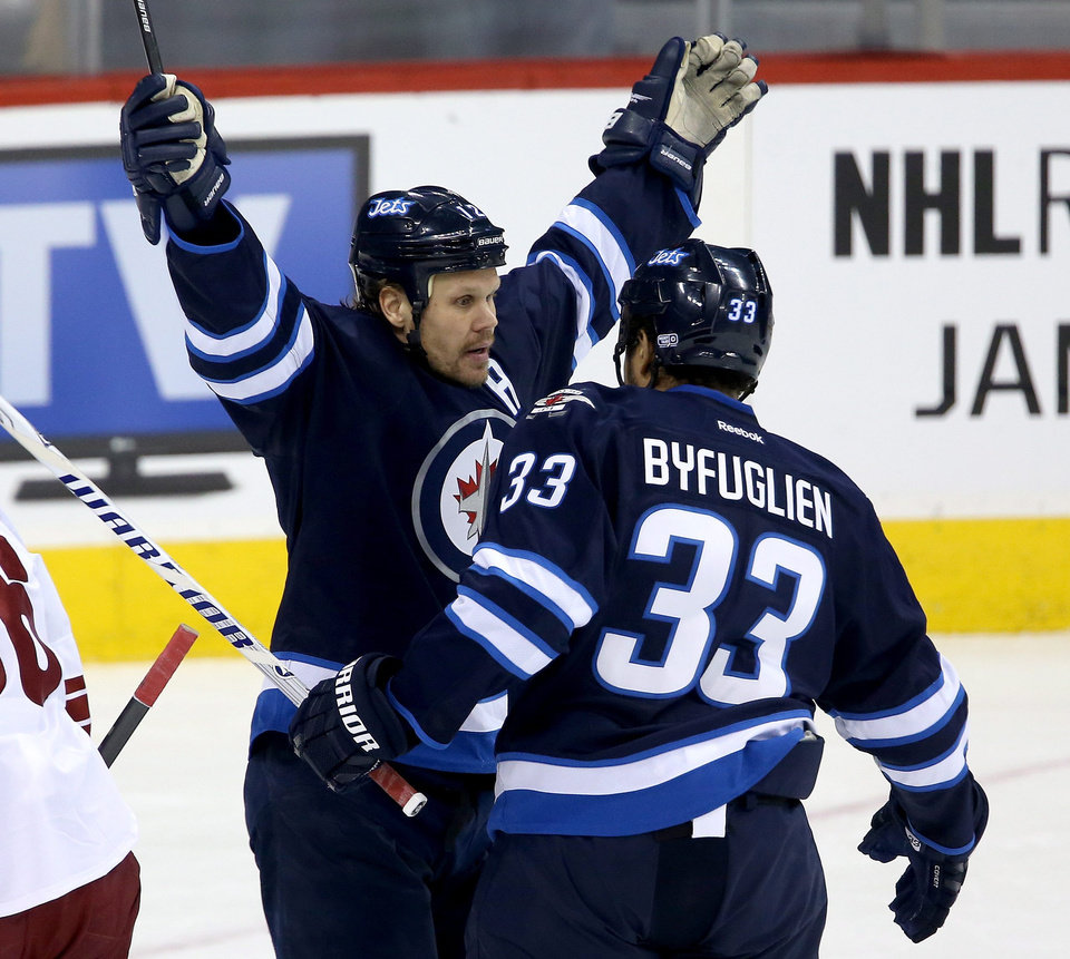 Photo - Winnipeg Jets' Olli Jokinen (12) celebrates with Dustin Byfuglien (33) after he scored his 12th goal of the season while playing against the Phoenix Coyotes' during first period NHL hockey action in Winnipeg, Monday, Jan. 13, 2014. (AP Photo/The Canadian Press, Trevor Hagan)