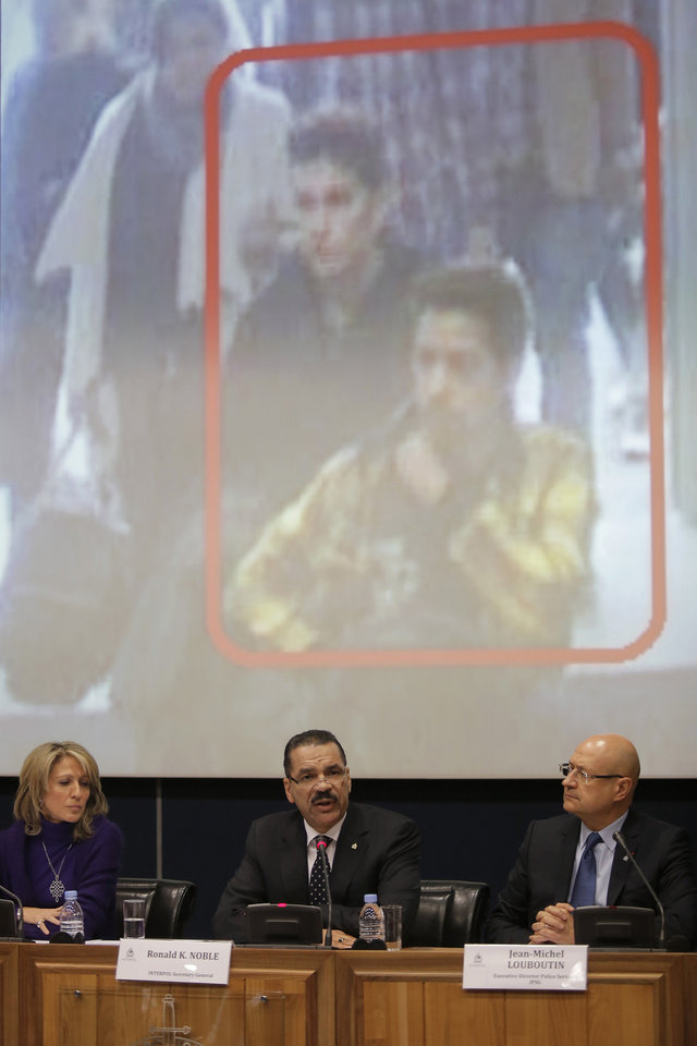 Photo - The image of two Iranian who were traveling with stolen passports on a missing  Malaysia Arlines jetliner is displayed on a screen during a presser at the Interpol headquarters in Lyon, central France, Tuesday, March 11, 2014. From left  Roraima Andriani, Interpol chief of staff, Ronald K. Noble, Secretary General of Interpol and Jean-Michel Louboutin, executive director police services.  (AP Photo/Laurent Cipriani)
