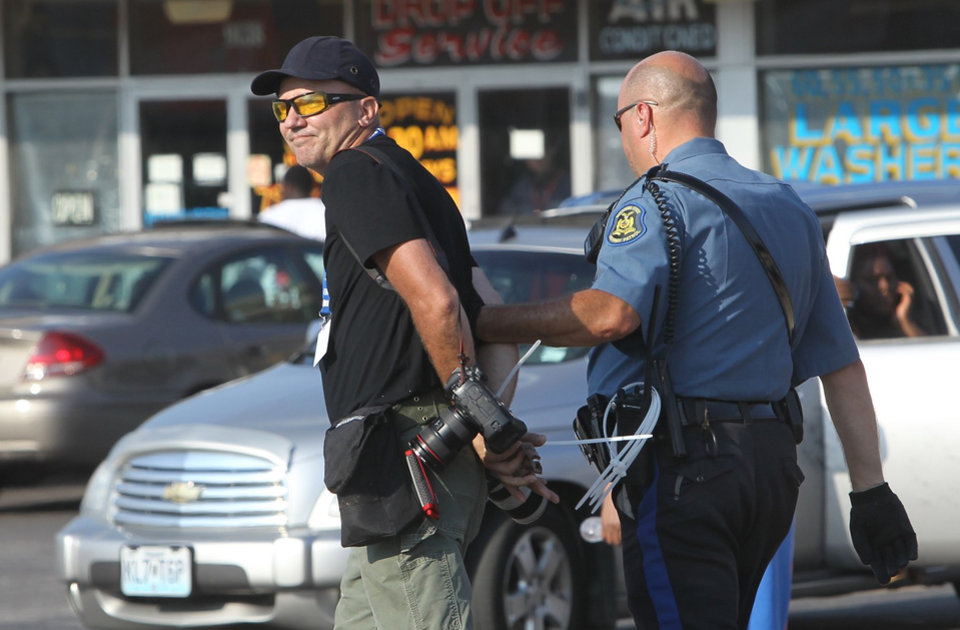 Photo - Getty Images photographer Scott Olson is arrested while covering demonstrators Monday, Aug. 18, 2014, in Ferguson, Mo. Missouri Gov. Jay Nixon called in the National Guard Monday after police again used tear gas to quell protesters in the wake of the shooting of Michael Brown.  (AP Photo/St. Louis Post-Dispatch,  J.B. Forbes)