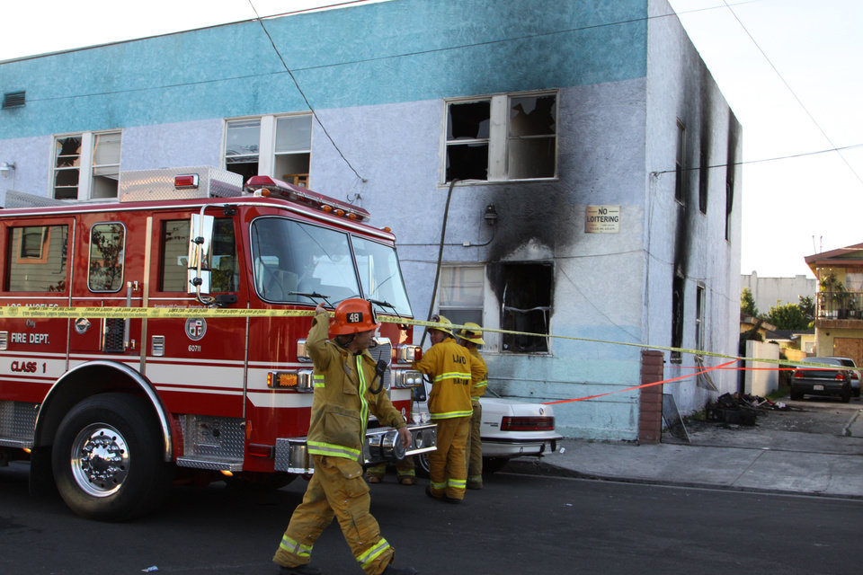 Photo - Fire roared through the Palos Verdes Inn, a 90-year-old residential hotel in the harbor area, early Tuesday, Jan. 22, 2013, injuring 14 people, three of them critically, in San Pedro, Calif. People hung out of windows of the Palos Verdes Inn  after the fire broke out at about 3:30 a.m., and one woman jumped from a second-story window and may have broken bones, Fire Department spokesman Erik Scott said. (AP Photo/The Daily Breeze, Chuck Bennett)  MAGS OUT; NO SALES