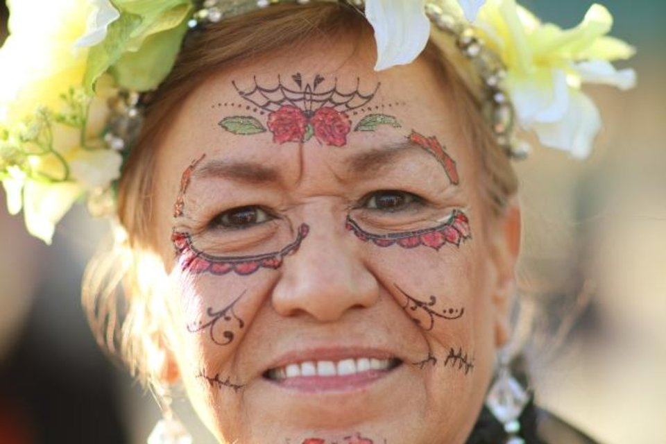 Photo -  Belinda Woods, of Yukon, smiles during the Day of the Dead Festival in the Plaza District. [DOUG HOKE/THE OKLAHOMAN]