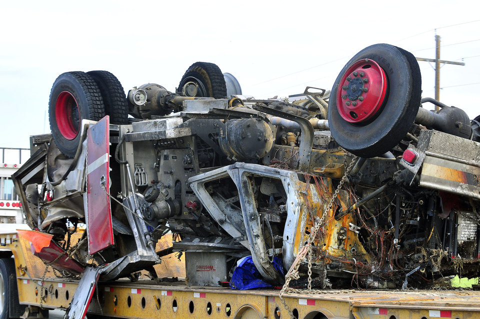 Photo - The wreckage of a Three Forks fire engine is loaded on a semi and hauled away from the scene of a fatal crash on Friday, June 20, 2014 near Helena , Mont. A fire engine and a pickup truck collided on the highway in southwestern Montana, causing an explosion and fire that killed six people, including a fire chief and three Helena children. There were no survivors. A Three Forks fire engine heading east on U.S. Highway 12 collided with a westbound pickup Thursday night, about 10 miles east of Helena, forcing both vehicles into the ditch, Jefferson County Sheriff's Deputy Bob Gleich said.  (AP Photo/The Independent Record, Eliza Wiley)