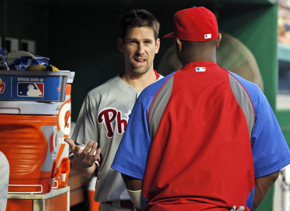 Photo - Philadelphia Phillies starting pitcher Cliff Lee, left, talks with Ryan Howard during the fourth inning of a baseball game against the Washington Nationals at Nationals Park Thursday, July 31, 2014, in Washington.  Lee left the game during the third inning. The Phillies announced that Lee had a recurrence of the left flexor pronator strain that sidelined him in May. (AP Photo/Alex Brandon)