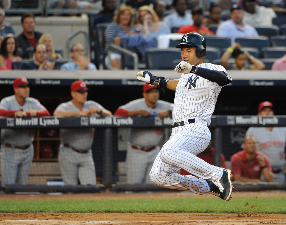 Photo - New York Yankees' Derek Jeter starts to slide safely into home plate to score on Carlos Beltran's single off Cincinnati Reds starting pitcher Mike Leake in the third inning of an interleague baseball game at Yankee Stadium on Friday, July 18, 2014, in New York. (AP Photo/Kathy Kmonicek)