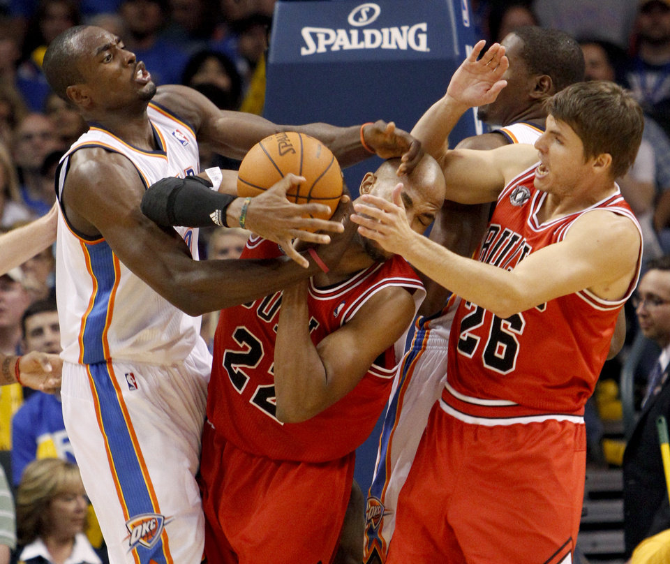 Photo - Oklahoma City's Serge Ibaka fights with Chicago's Taj Gibson, center, and Kyle Korver for the ball during the NBA basketball game between the Oklahoma City Thunder and the Chicago Bulls in the Oklahoma City Arena on Wednesday, Oct. 27, 2010. Photo by Bryan Terry, The Oklahoman