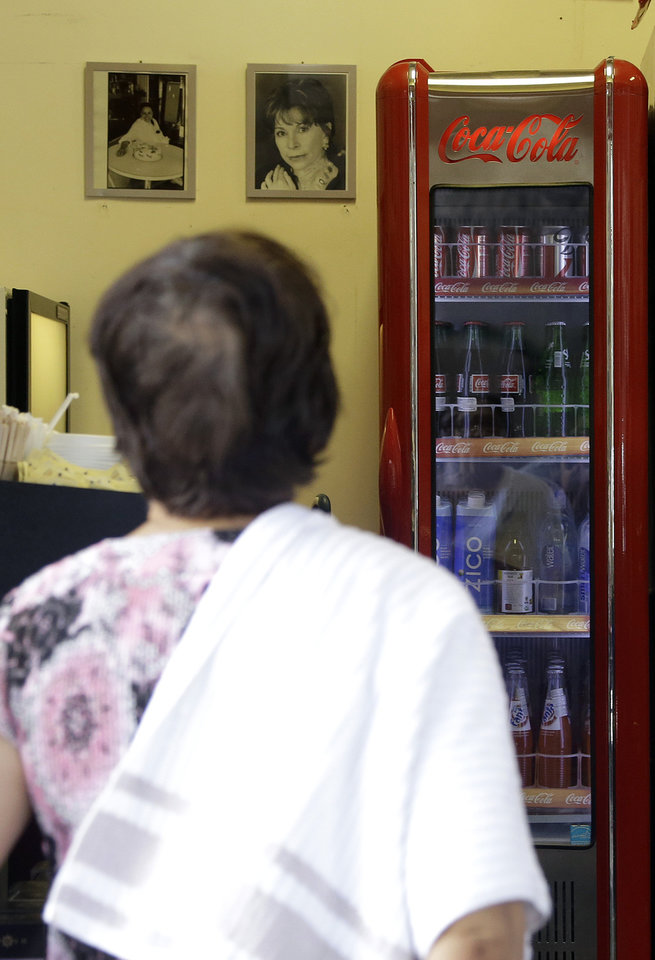 Photo - In this June 30, a customer looks toward a refrigerator holding sodas and other drinks as she orders food at Chile Lindo in San Francisco. San Francisco and Berkeley are aiming to become the first U.S. cities to pass per-ounce taxes on sugary drinks. (AP Photo/Jeff Chiu)