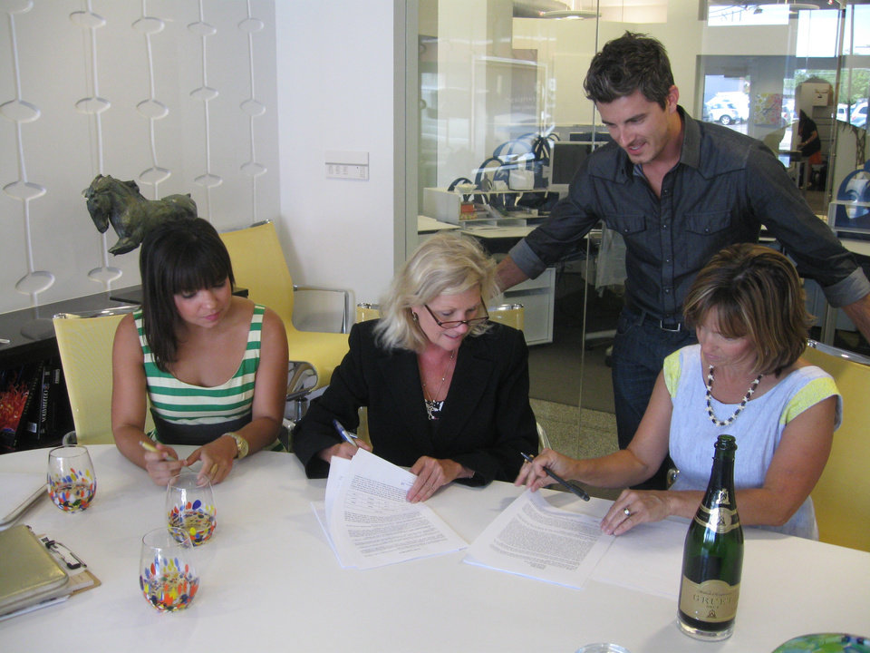Brittney Melton, Chris England and Traci Walton sign a lease with their new landlord, Meg Salyer, center, for their new shop Plenty Mercantile along Automobile Alley in Oklahoma City. Photo by Steve Lackmeyer, The Oklahoman