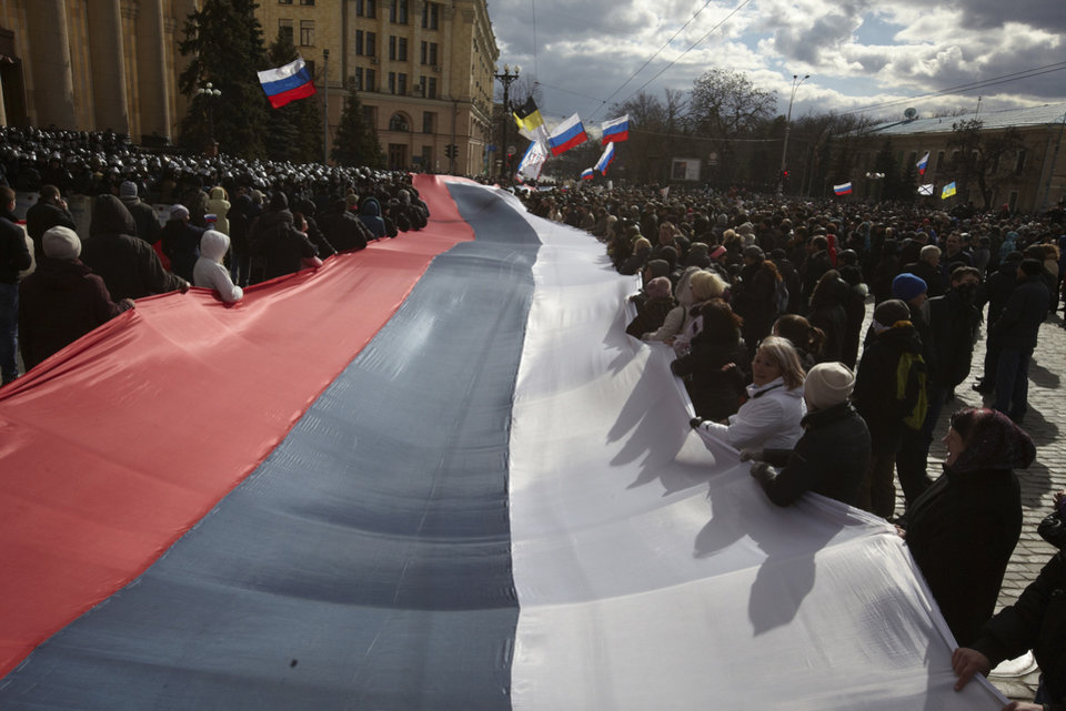 Photo - In this photo taken on Sunday, March  16, 2014, Pro-Russia demonstrators chant slogans as they carry a giant flag during a rally at a central square in Kharkiv, Ukraine. Thousands of pro-Russia demonstrators gathered in the Ukraine's northeastern town to show their support for the Crimean referendum. (AP Photo/Sergey Kozlov)