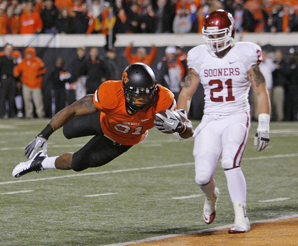 Photo - OSU's Jeremy Smith (31) flies into the end zone for a touchdown past OU's Tom Wort (21) in the first quarter during the Bedlam college football game between the Oklahoma State University Cowboys (OSU) and the University of Oklahoma Sooners (OU) at Boone Pickens Stadium in Stillwater, Okla., Saturday, Dec. 3, 2011. Photo by Nate Billings, The Oklahoman
